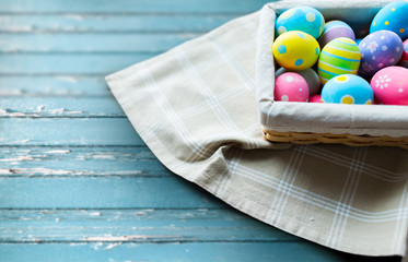 easter, holidays and object concept - close up of colored eggs in basket over blue vintage wooden boards background