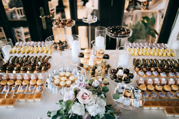 Beautifully decorated wedding dessert table with cakes and echleurs and other sweets