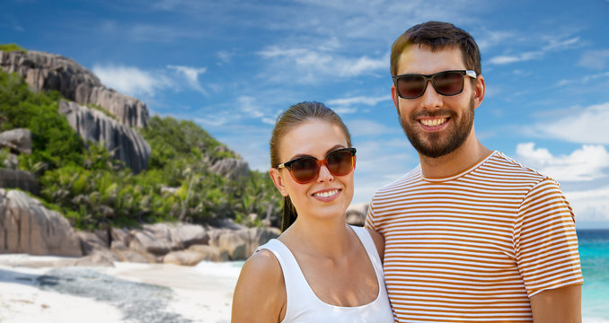 travel, tourism and people concept - happy couple in sunglasses outdoors over tropical beach on seychelles island background