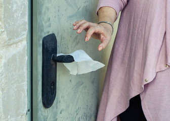 Woman puts a napkin on the door handle to open it