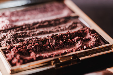 palette with crushed powder eyeshadows in nude and blush tones on dark background