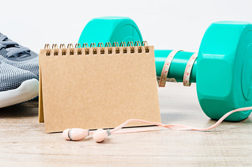 Blank diary with sneakers and dumbbells.