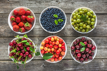 Fresh berries in a bowls. Variety of berry fruit on table, top view, flat lay.