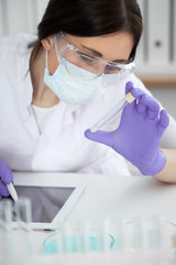Close-up of professional female scientist in protective eyeglasses making experiment with reagents in laboratory or making blood tests. Medicine, science and research concept