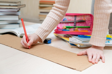 child draws on a piece of cardboard. close-up. there are books and pencils nearby