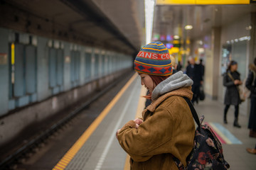 Beautiful young asian woman traveler looking watch  ,Waiting for train at train station, Travel and vacation concept.