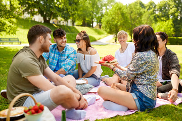 friendship, leisure and summer concept - group of happy friends eating watermelon at picnic in park Wall mural