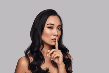 Can you keep a secret? Beautiful young woman looking at camera and keeping finger on lips while standing against grey background