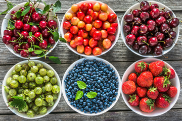 Fresh berry fruits in a bowls, flat lay. Variety of berries, background