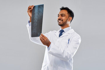 medicine, healthcare and people concept - smiling indian doctor looking at spine x-ray over grey background