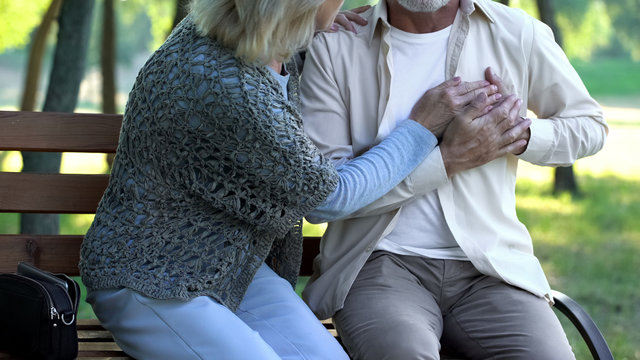 Pensioner suffering heart pain, walking in park, scared wife supporting him