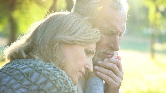 Sad senior wife embracing crying husband, relative loss, grief and sorrow