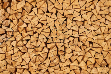 Background image of stacked, dry chopped logs used for firewood. Pile of logs ready to be used in fireplace. Alternative warming method.
