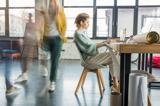 female architect sitting and using laptop at desk in loft office with colleagues in motion blur on background