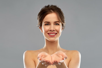 beauty and people concept - smiling young woman with bare shoulders holding something imaginary over grey background
