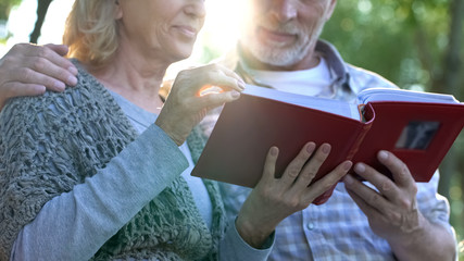 Happy moments, adult parents admiring photos in family album remembering youth