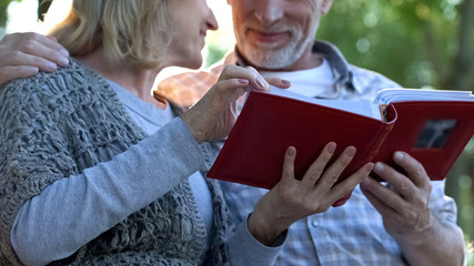 Adult parents admiring photos in family album remembering youth, happy moments