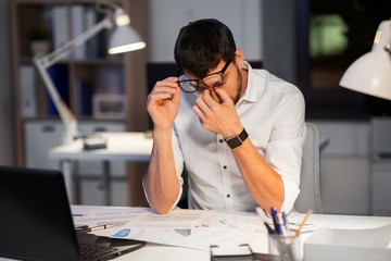 business, deadline and stress concept - tired businessman in eyeglasses working at night office Wall mural