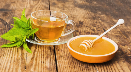 Cup of green tea mint honey on wooden background