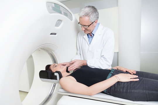 young lady with the doctor in the room of computed tomography at hospital.