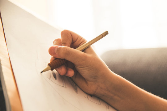 Close up view of a young hand drawing on a white sheet. Kid hold a black wooden pencil and draw something on a warm orange light at home. Children writing on a paper. Teen drawing freehand a manga.
