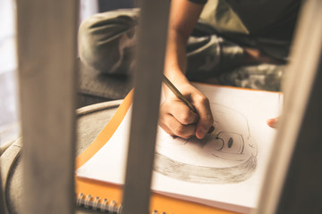 Close up view of a young hand drawing a face on a white sheet. Kid hold black wooden pencil and draw something, warm orange light at home. Children writing on a paper. Teen drawing freehand a manga.