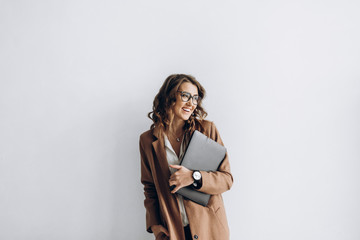 Happy business woman in a glasses with a laptop in her hands in the office with copy space Wall mural