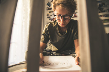 Close up bottom view of a young boy drawing a face on a white sheet. Kid hold a pencil and draw something, warm orange light at home. Children writing on a paper. Teen drawing freehand a manga