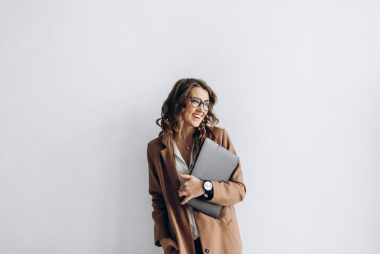 Happy business woman in a glasses with a laptop in her hands in the office with copy space