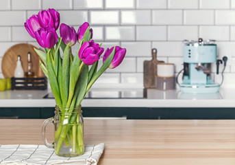 Purple tulips in a glass jar standing on the modern kitchen