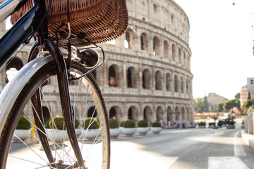 Close-up bike's wheel in front of colosseum in Rome at sunset.