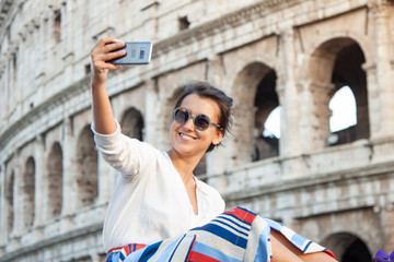 Beautiful young woman taking selfie pictures with smartphone sitting in front of colosseum in Rome at sunset.