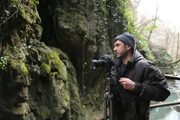 man with camera and tripod in a forest in the mountains