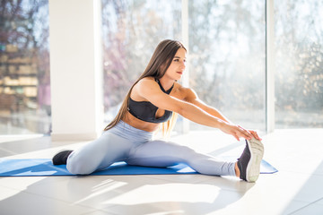 Young beautiful girl wearing fashion sports wear doing exercise stretching the legs on mat at gym with big windows