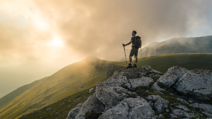 Young hiker man with backpack and walking poles, standing on peak of a mountain looking at sunset in cloudy sky. Green field and rocks. Abruzzo, Italy. Fototapete