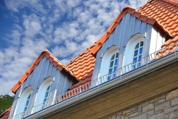 Neu renovierte Dachgauben mit Holzplanken-Verkleidung als Wetterschutz an einem denkmalgeschützten Wohngebäude