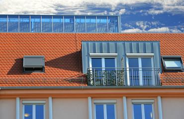 Dachgaube mit Stehfalz-Zinkblechverkleidung Außenrollladen und Geländer an einem Giebeldach mit zentralem Glasaufbauals Wetterschutz an einer modernen Senioren-Residenz