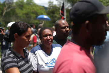 People wait for information in front of the Flamengo soccer club's training center, after a deadly fire, in Rio de Janeiro