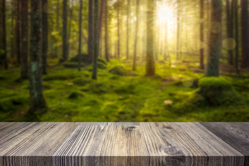 Empty table top for product display montage. Green sunny forest blurred in the background.