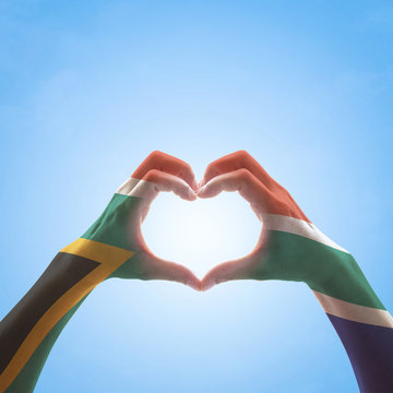 South Africa flag on woman hands in heart shape isolated on blue sky background for national unity, union, love and reconciliation concept.