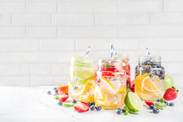 Selection various fruit and berry lemonade drinks, refreshment infused water, in mason jars, with fresh strawberry, lemon, lime, oranges, blueberry,  copy space