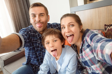 Family at home sitting on couch in living room together taking selfie pictures tongue out playful