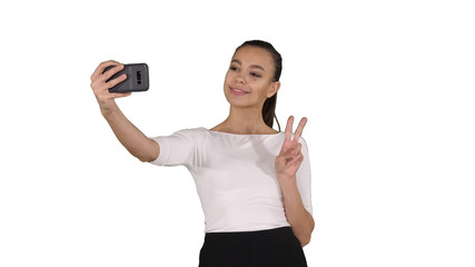 Smiling attractive woman taking a selfie while walking on white background.