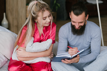 Happy together. Young family in bed making morning notes.