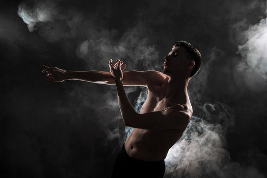 A young male ballet dancer with black leggings and a naked torso performs dance moves against a gray grunge background, with a light of lights and smoke.