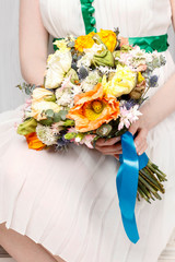 Woman in white dress holding a wedding bouquet of poppies and carnations.