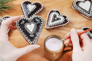 Woman decorating gingerbread cookies in heart shape.