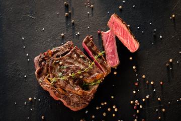 Restaurant cooking art. Grilled steak sliced on textured black background.