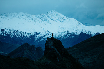 Person standing on mountain peak during winter Wall mural