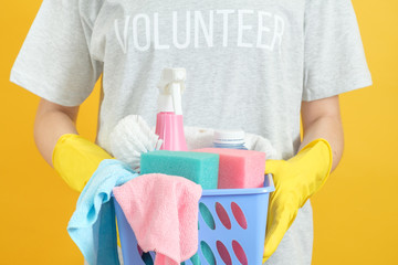 House cleaning volunteer. Torso with basket of supplies. Hands in yellow rubber gloves.